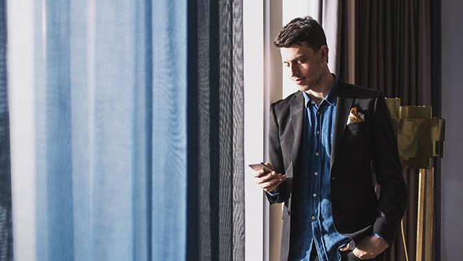 Man looking at phone in hotel room